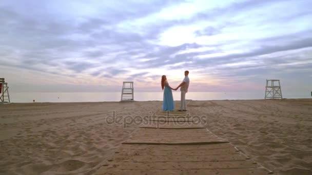 Paar halten Hände am Meeresstrand. Liebe paar Strand Sonnenaufgang. Schwangere paar