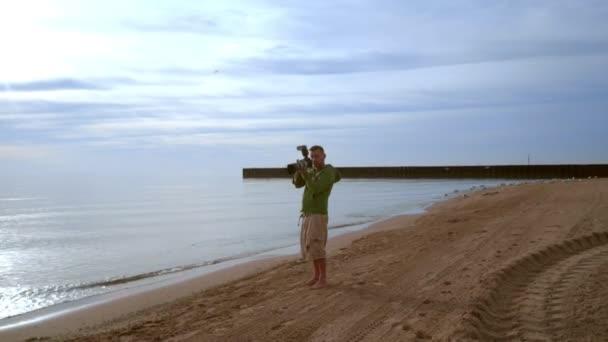Fotograf s kamerou na pláži moře. Fotograf fotografování