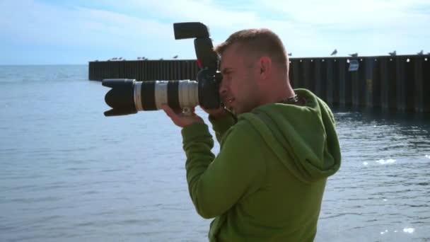Fotografo che cattura foto alla spiaggia del mare. Chiuda in su del fotografo con la macchina fotografica