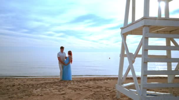 Pregnant couple beach. Love couple beach. Couple looking at each other