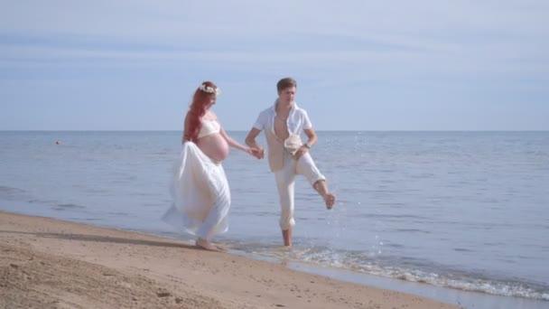 Liebe Paare, die Spaß am Strand. Schwangere paar Spritzwasser