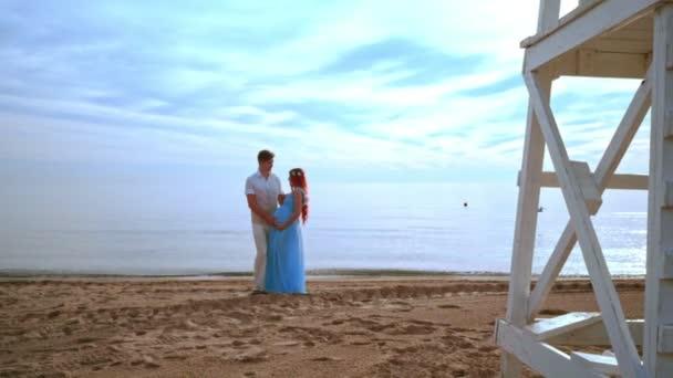 Werdende Eltern am Strand. Schwangere paar Bauch mit Liebe und Sorgfalt zu berühren