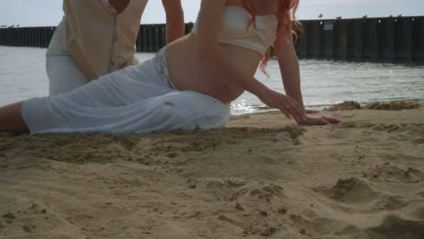 Schwangere paar am Strandsand zeichnen. Liebespaar am Strand entspannen