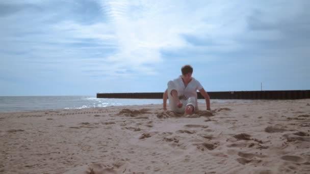 A férfi feküdt a homokba. Ember beach feláll és megy ki a keret
