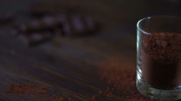 Hořká čokoláda a kakao prášek ve sklenici na dřevěný stůl. Nasekané čokolády