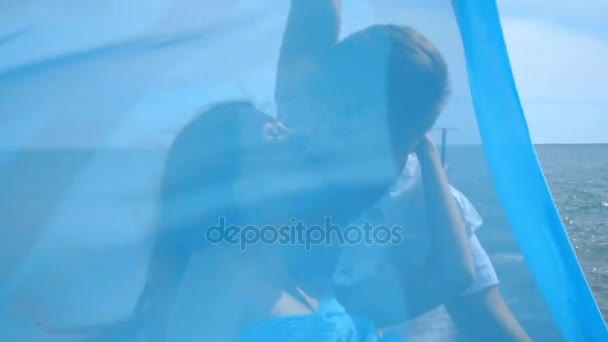 Love couple kissing. Happy woman kissing man behind blue cloth. Happy family