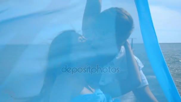 Láska, pár líbání. Šťastná žena líbala muže za modrým ubrouskem. Šťastná rodina