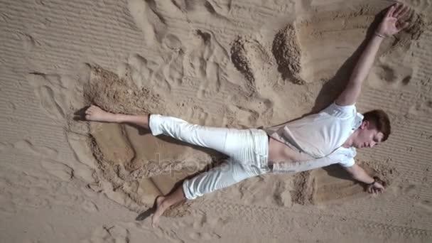 Ember parton pihenjen. A férfi feküdt a homokba. Pihenjen a tengerparton. Ember pihentető, homok
