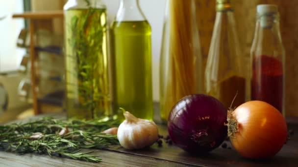 Složky potravin na kuchyňském stole. Detailní záběr na cibuli, česnek a rozmarýn bylina