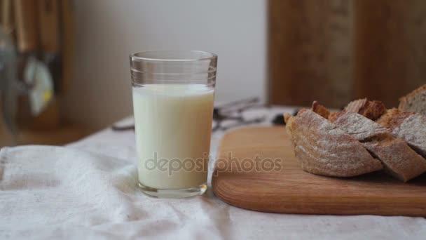 Sklenici mléka a chleba plátek na dřevěné desce. Pohár mléka a krájený chléb