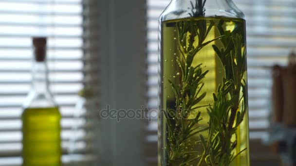 Olive oil with rosemary. Rosemary herb falls in olive oil bottle
