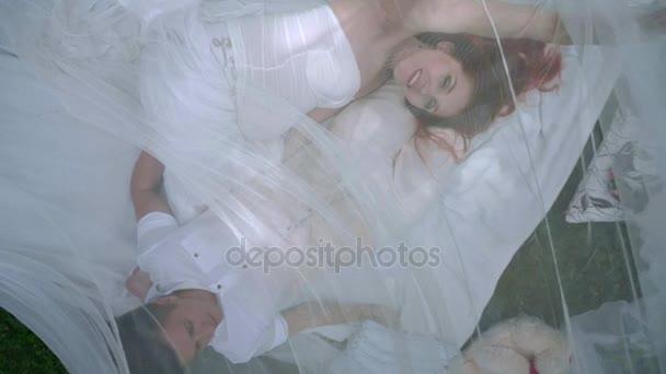 Pohled shora lásky pár odpočinkem na bílé látky za průhledný závoj v parku