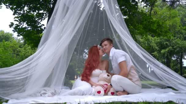 712ba65e97 Romántica pareja besándose en decoraciones para sesión de fotos de boda en  el Parque– metraje de stock