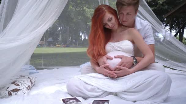 Láska pár drží za ruce ve tvaru srdce na těhotné bříško