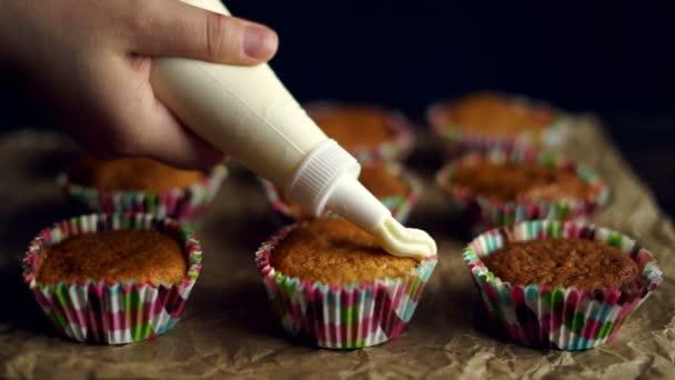 Cupcake mázolás. Kezei csővezeték táskát tele krém