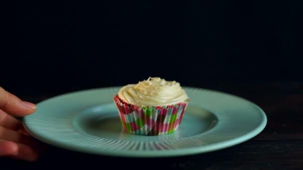 Ženská ruka odnést košíček na keramické desce. Chutné muffin dort