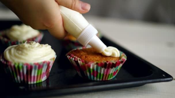 Cuoco unico che fa di muffin. Decorazione di muffin. Cupcakes decorare con panna montata