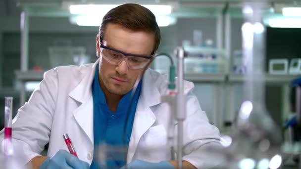 Vědec kontrola zkumavky s růžovou kapalinou. Laboratorní pracovník