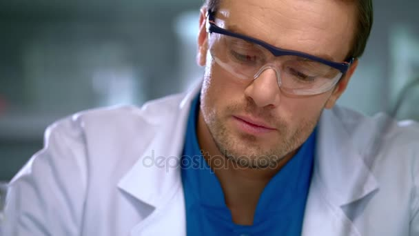 Muž vědec v laboratoři. Zblízka scientisti člověka při pohledu na kapalinu v baňce