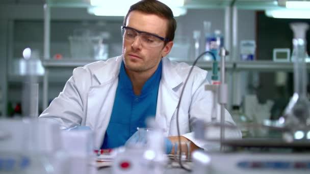 Vědci v laboratoři. Vědec, při pohledu na chemické roztoky ve výzkumné laboratoři