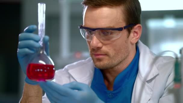 Chemik v laboratoři. Mužské chemik tekutina ve skleněné baňce při pohledu zblízka