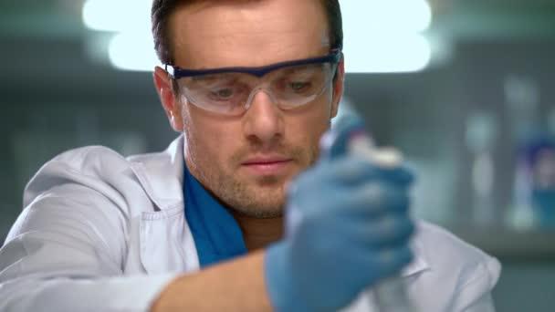 Vědec pomocí pipety v laboratoři. Vědec pomocí kapátka