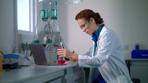 Vědec najít lék. Vědec žena při pohledu na chemické kapaliny v laboratorní baňky