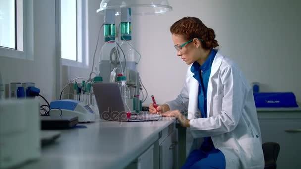 Výzkumník v laboratoři. Mladá žena pracující v moderní laboratoř. Vědec výzkumu