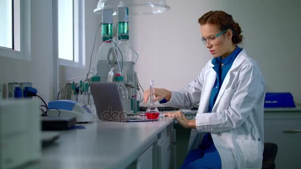 Woman scientist studying chemical liquid in lab flask. Chemical engineering