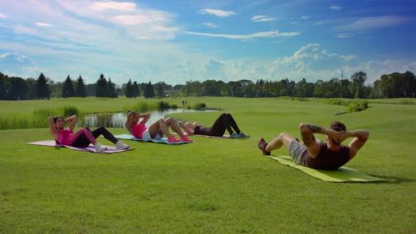Fitness csoport felülés személyi edzővel. Kültéri fitness osztály