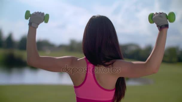 Přizpůsobit žena výtah váhy venku. Zadní žena cvičení s činkami v parku