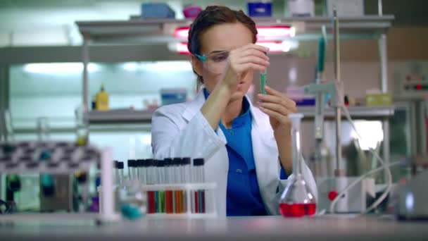 Female chemist in laboratory. Chemist analyzing chemical liquid in ...