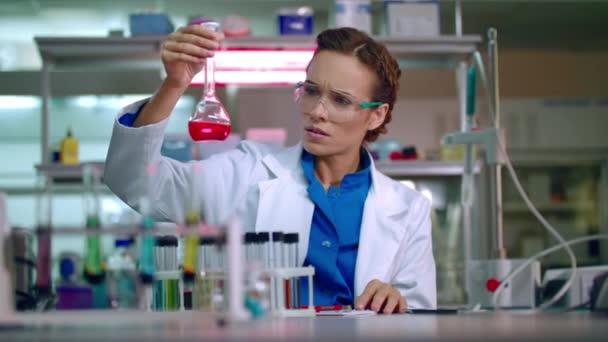 Chemik v laboratoři. Ženské chemik pracující s chemickými kapalina v chemické laboratoři
