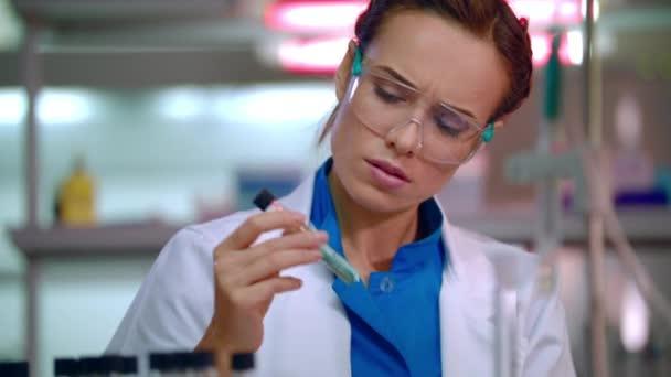 Lékařský výzkumník v laboratoři. Zblízka vědce míchání kapaliny ve zkumavce