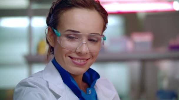 Happy výzkumník v laboratoři. Laboratoře resercher tvář v ochranné brýle. Žena vědec