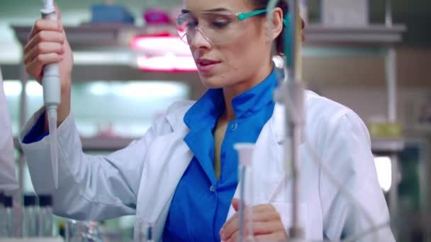 Ömlött a folyadékot a mérőlombikba pipettával kémiai Lab tudós hallgatói