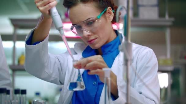 Vědec žena pracující s chemickými činidly. Chemické reakce v laboratorní baňky