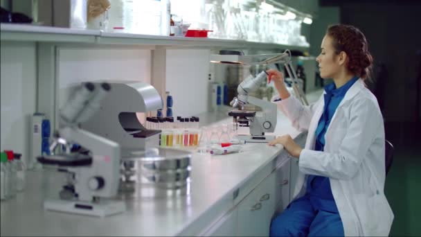 Woman scientist start working with microscope. Microbiologist looking microscope