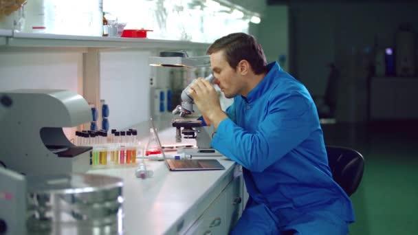 Mužské chemik v chemické laboratoři. Chemie vědec vypadající mikroskop