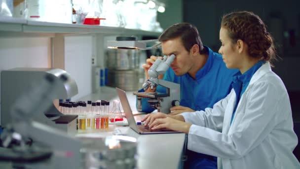 Laboratoře výzkumných pracovníků pracujících s výzkumný mikroskop. Vědecký tým, pracující v laboratoři