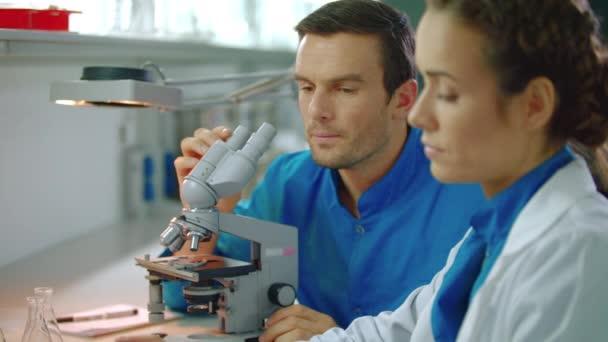 Tým lékařů pracujících v laboratoři. Laboratorní vědec, který pracuje s mikroskopem a tablet pc