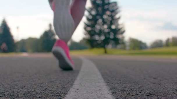 Africká žena nohy v sportovní boty začne běžet po asfaltové silnici