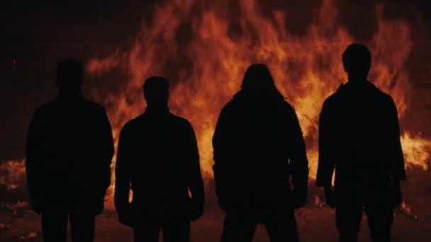 Sziluett férfi állandó tűz háttér. Négy férfi állandó tűz ég