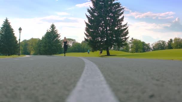 Fitness žena běží venku. Běžkyně školení na park road