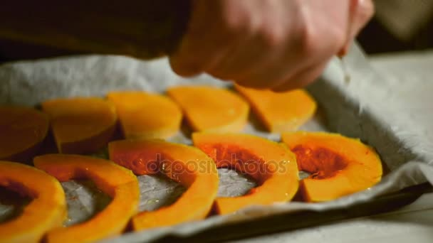 Pumpkin pieces pouring olive oil. Baked vegetables cooking. Pumpkin dish