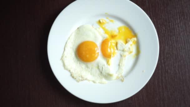 A nő kezét vágás darab sült tojás a kést és a villát felülnézet