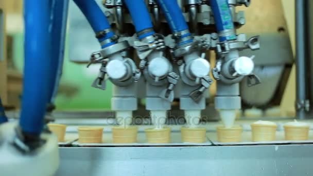 Food processing equipment. Waffle cones filling with ice cream. Production line