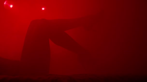 Silhouette of sexy woman feet in red light. Hot girl legs in high heel shoes