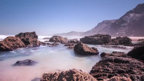 Příliv a odliv moře modré vody na skalnaté pobřeží. Mořský vánek nad úvodní vlny
