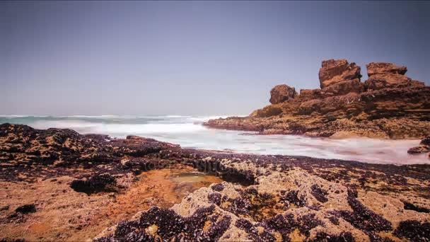 Ocean wave fleky na kamenité pláži. Pěnové vlna stříkající na skalnaté pobřeží